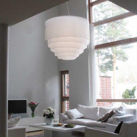 Petri Vainion suunnittelema kankainen Vuolle-valaisin pehmentää kauniisti korkeaa ja minimalistisesti kalustettua tilaa.