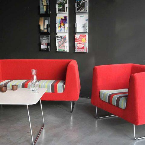 Yrityksen aulatilaan on luotu reipas ja raikas tunnelma isoilla kontrasteilla. Nojatuolien vahva väritys leiskuu tummaa seinää vasten, jolta myös esitetelineet nousevat taulumaisena esineenä esille.